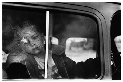 "USA. Colorado. 1955. Boy looking through a cracked window. From ""Personal Exposures"" pg 253. ©Erwitt/Magnum Photos"