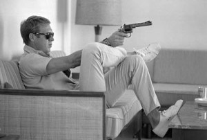 John Dominis: Steve McQueen aims a pistol in his living room.