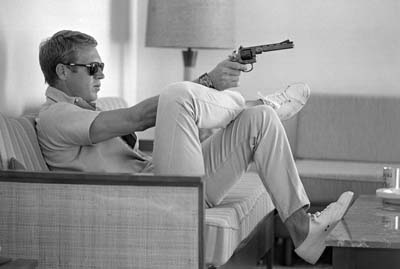 John Dominis: Steve McQueen aims a pistol in his living room.